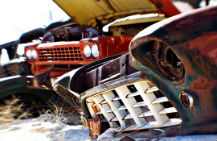 several older model cars in a salvage yard